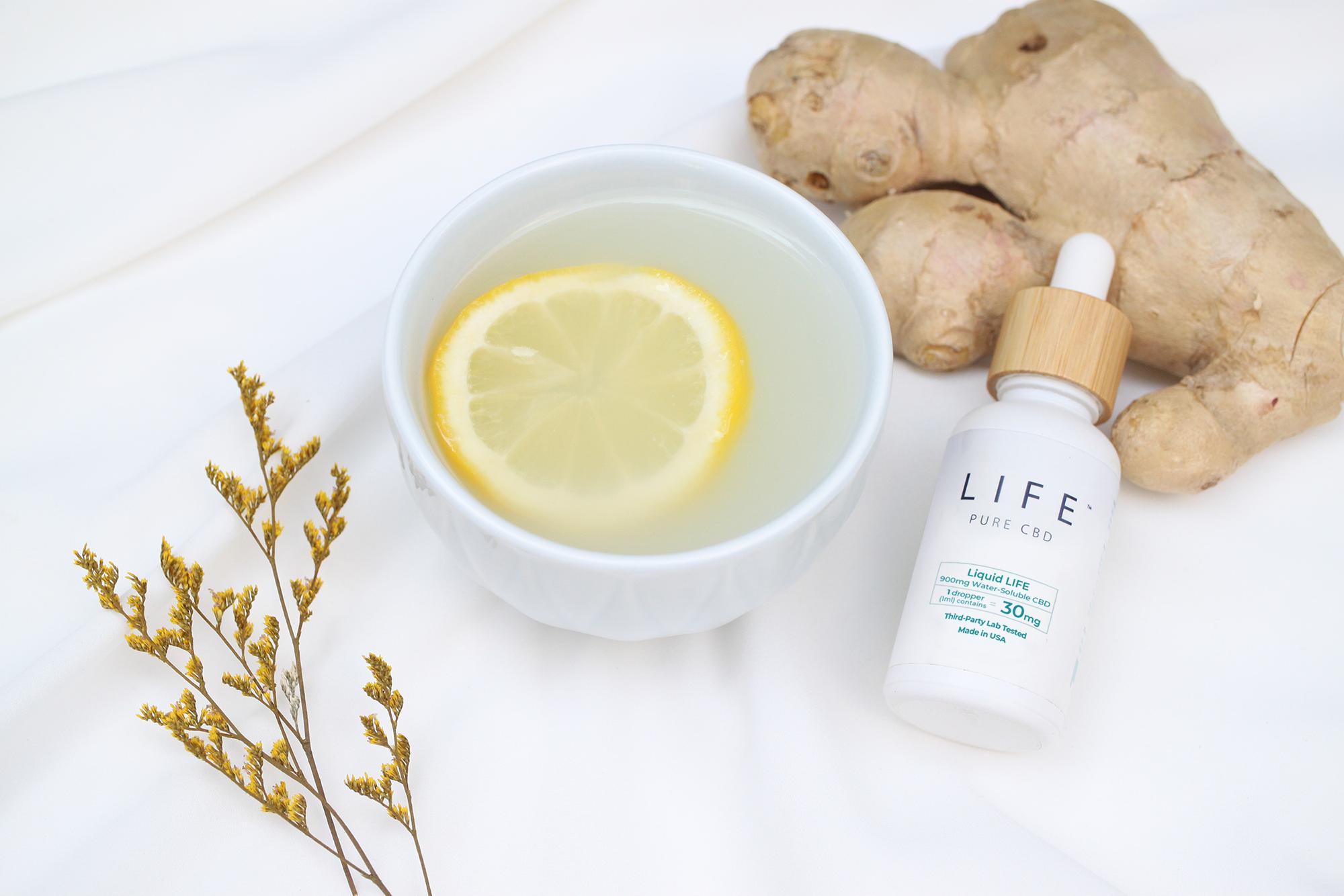 A cup of hot lemon tea with ginger alongside a bottle of Liquid LIFE